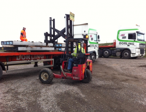 Truck mounted forklift delivering precast concrete floor sections
